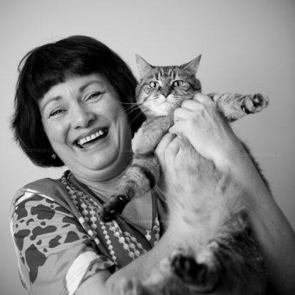 lady holding up pet cat.